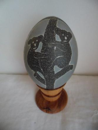 carved Emu egg with Emus and Koalas on timber stand